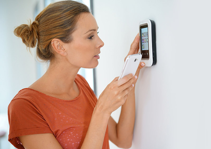 Women holding smartphone & looking at thermostat.